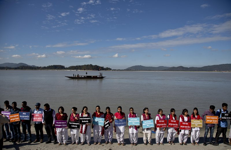 In this Monday, Dec.11, 2017 photo, students from India's northeastern Assam state hold placards by the Brahmaputra river during a protest against the contamination of the river in Gauhati, India. Officials in India's northeast are complaining that Chinese construction activity on the upper reaches of one of the largest rivers that flows into India are likely turning the waters downstream turbid and unfit for human consumption.