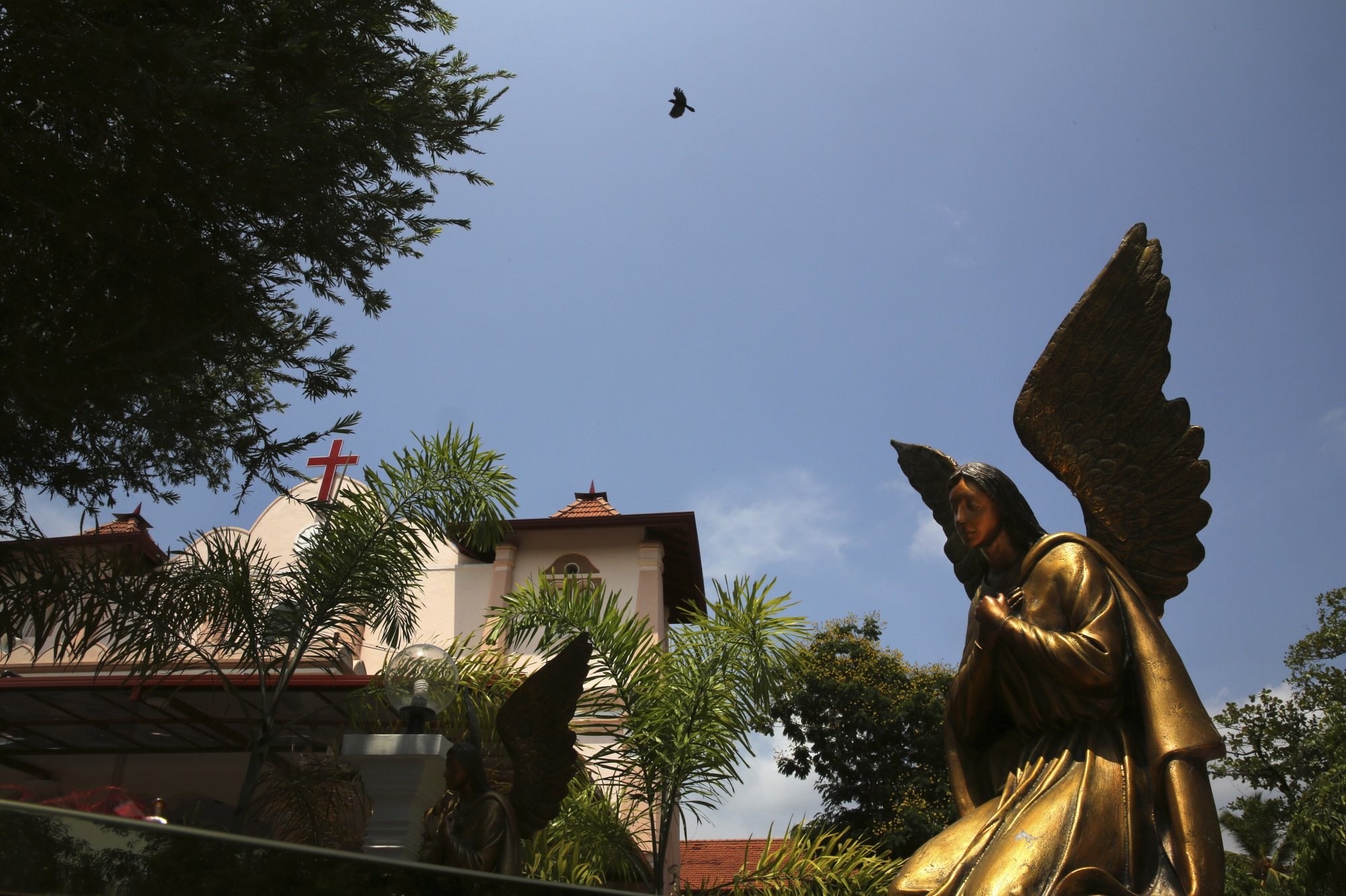 In this Thursday, April 25, 2019 photo, a bird flies over St. Sebastian's Church, where a suicide bomber blew himself up on Easter Sunday in Negombo, north of Colombo, Sri Lanka. Nearly a week later, the smell of death is everywhere, though the bodies are long gone. From inside, you see destruction wherever you look. But from outside the church, if you ignore the police tape and if you're standing far enough away, you might think nothing had happened there at all. (AP Photo/Manish Swarup)