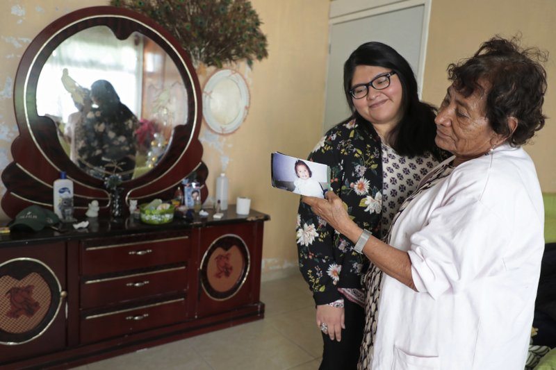 In this Dec. 23, 2016 photo, Tamara Alcala Dominguez spends time with her grandmother Petra Bello Suarez in their home town of Molcaxac, Puebla state, Mexico, during her first return home since she left Mexico for the U.S. as a toddler. With her grandmother now 75 years old and suffering from hypertension, diabetes and other ailments, Alcala was determined not to repeat the anguish she felt when her grandfather died of prostate cancer before she could see him. A special program allowed her to make her first journey back to Mexico, and return safely. (AP Photo/Pablo Spencer)