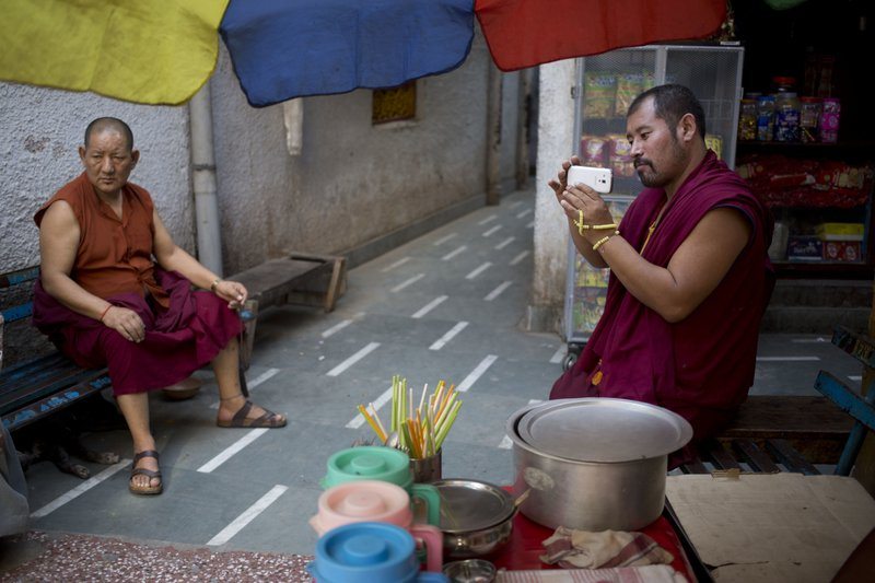An exile Tibetan monk takes pictures on his mobile sitting outside a temple in New Delhi, India, Tuesday, April 4, 2017. India said Tuesday that China should not interfere in its internal affairs, as the Dalai Lama began a weeklong visit to India's remote northeast that Beijing has protested.