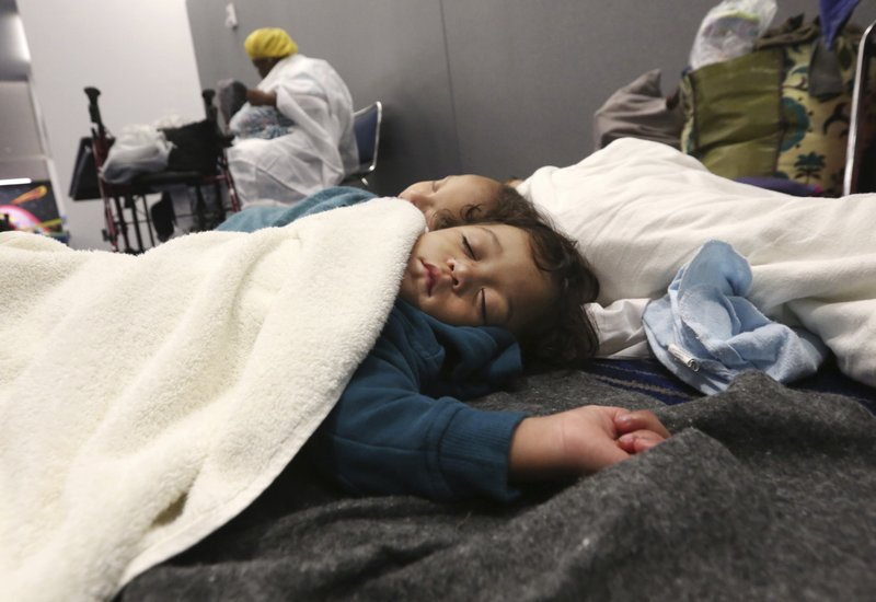 Robert Salgado, 2, sleeps on the floor at the George R. Brown Convention Center that has been set up as a shelter for evacuees escaping the floodwaters from ...
