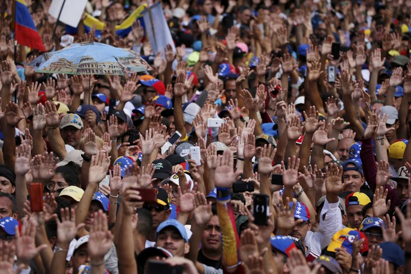 Anti-government protesters hold their hands up during the symbolic swearing-in of Juan Guaido, head of the opposition-run congress, who declared himself interim president of Venezuela. (AP Photo/Fernando Llano)