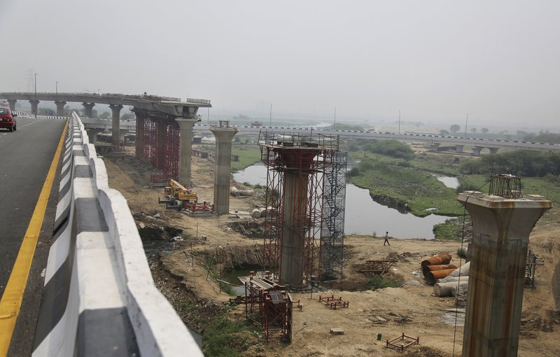 In this June 1, 2017, file photo, an Indian man walks beneath an under construction flyover in New Delhi, India. Three years later Prime Minister Narendra Modi came to power, India's economic prospects are looking decidedly more grim. India's economic expansion has slowed to its lowest level in three years. Small businesses are struggling, or even shutting down, after a major overhaul to both the country's currency and sales tax system.