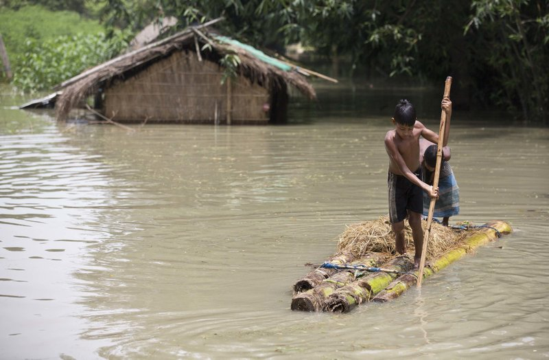Flood affected boys move on a banana raft near partially submerged houses in Morigaon district east of Gauhati, Assam, India, Tuesday, Aug. 15, 2017. Heavy monsoon rains have unleashed landslides and floods that killed dozens of people in recent days and displaced millions more across northern India, southern Nepal and Bangladesh.