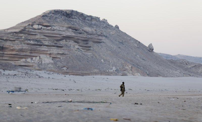 In this photo taken Monday, March 6, 2017, a Somali government soldier walks on the beach in Eyl, in Somalia's semiautonomous northeastern state of Puntland. Somali pirates have seized a small boat, kidnapped its Indian crew members, and are taking the vessel to the Eyl area of northern Somalia, an investigator said Monday, April 3, 2017, the latest vessel targeted by the region's resurgent hijackers.