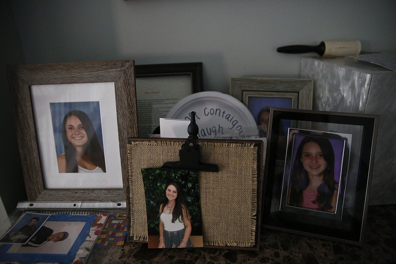 Photographs of Alyssa Alhadef, sit on a table in her home on Wednesday, Jan. 30, 2019, in Parkland, Florida. (AP Photo/Brynn Anderson)