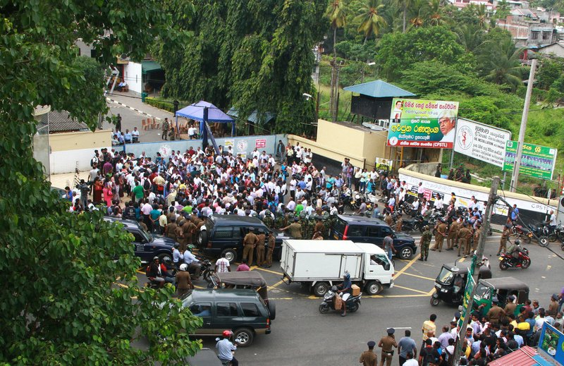 Union workers gather while on strike outside the main oil installation facility in Colombo, Sri Lanka, Wednesday, July 26, 2017. Sri Lanka's government has deployed army troops to restore fuel distribution crippled during a strike launched by trade unions who want to stop leases of oil tanks to India and China.