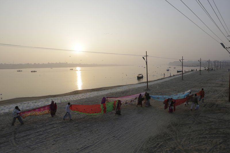 In this Thursday, Jan. 5, 2017, file photo, Hindu devotees dry their clothes after taking a dip at Sangam, the confluence of rivers Ganges, Yamuna, and mythical Saraswati in Allahabad, India. A court in northern India has granted the same legal rights as a human to the Ganges and Yamuna rivers, considered sacred by nearly a billion Indians. The Uttaranchal High Court in Uttarakhand state ruled Monday, March 20, 2017, that the two rivers be accorded the status of living human entities, meaning that if anyone harms or pollutes the rivers, the law would view it as no different from harming a person.
