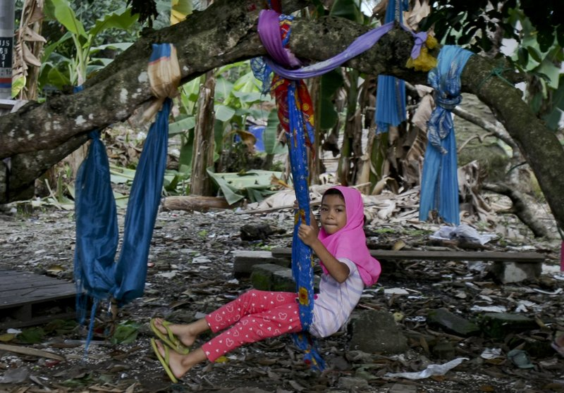 In this Tuesday, Sept. 12, 2017, photo, a Rohingya Muslim girl living in Malaysia sits on a makeshift swing outside her house in Klang, outside Kuala Lumpur, Malaysia. Recent violence in Myanmar has driven hundreds of thousands of Rohingya Muslims to seek refuge across the border in Bangladesh. There are some 56,000 Rohingya refugees registered with the U.N. refugee agency in Malaysia, with an estimated 40,000 more whose status has yet to be assessed.