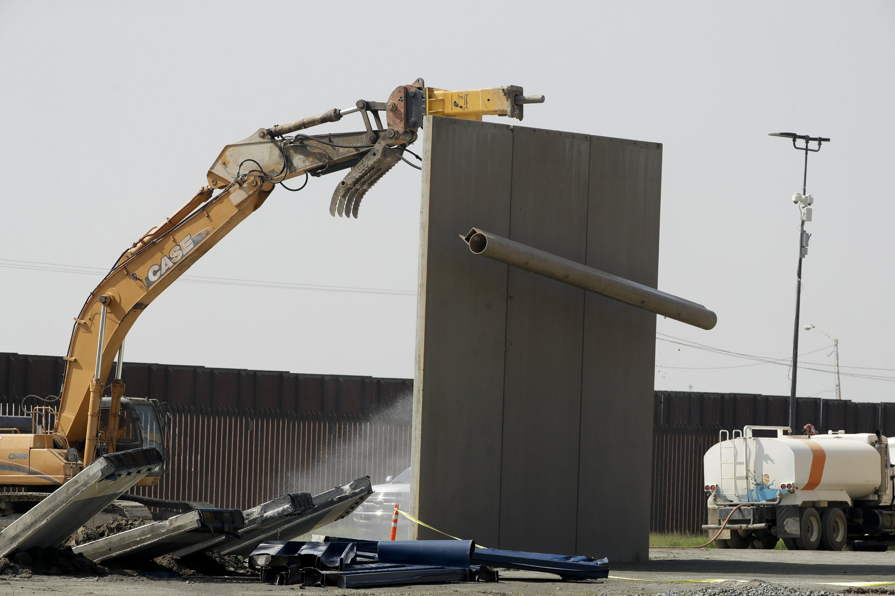 Amid clouds of dust, border wall prototypes are demolished