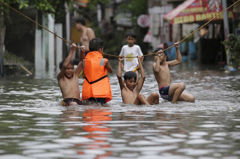 "In this Thursday, July 27, 2017, file photo, boys play outside their flooded homes after heavy rains from tropical storm ""Nesat"" flooded parts of metropolitan Manila, Philippines. Strong rains caused floods in low-lying areas and classes were suspended in most schools in the capital."