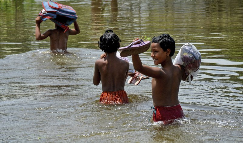In this Saturday, Aug. 19, 2017, file photo, schoolchildren wade past floodwaters in Gaibandha district, about 120 miles (192 kilometers) north of capital Dhaka, Bangladesh. This week's flooding in Houston is unprecedented, but such devastation is chronic across South Asia. Experts say local officials are ignoring dangers and pursuing development plans that only increase the risk of flood-related death and destruction as annual monsoon rains challenge cities to cope.