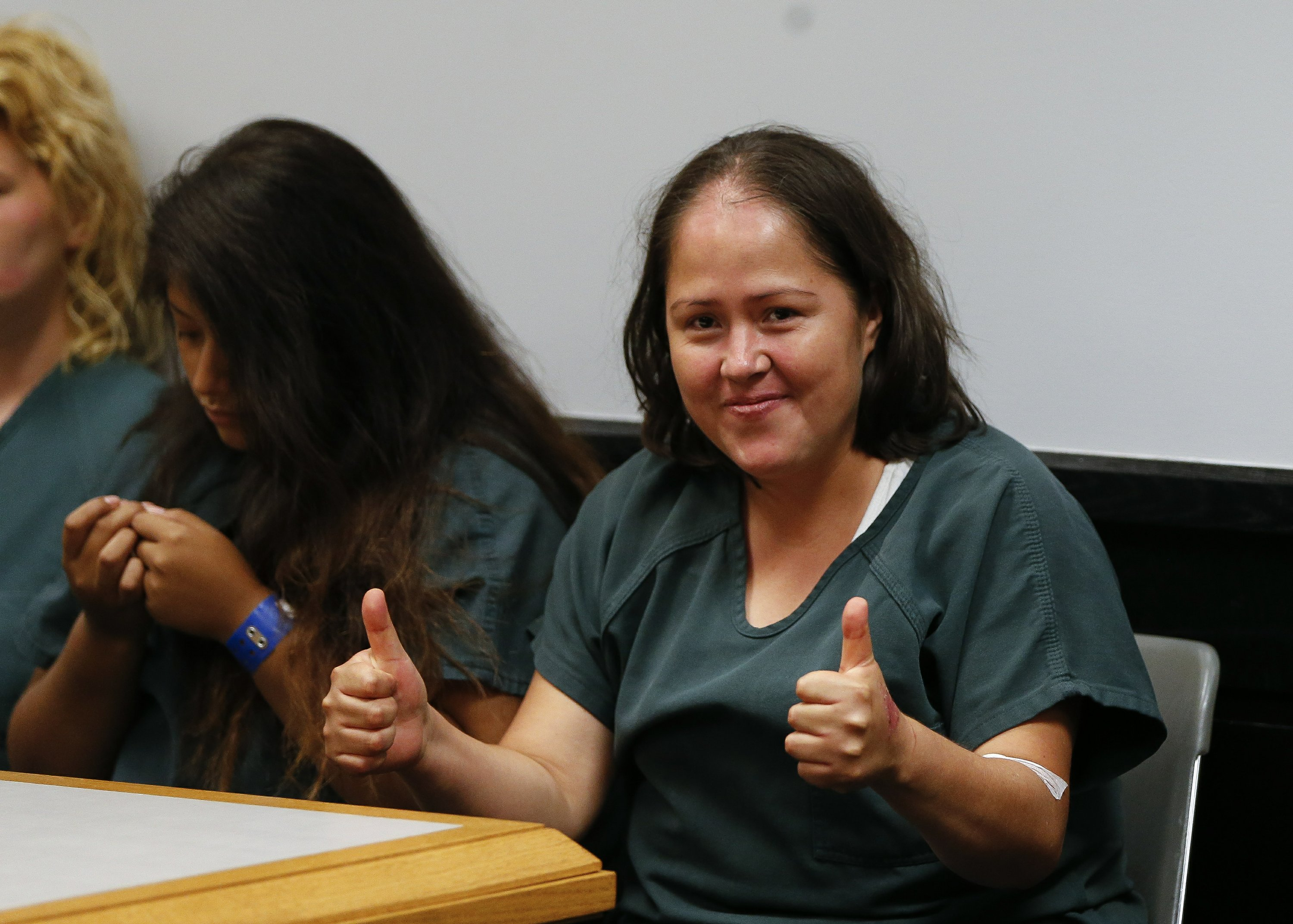 Smiles and thumbs up from woman charged with killing family