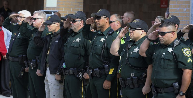 The latest deputy killed responding to manhunt identified orange county sheriff deputies salute as the body of orange county sheriffs office deputy first class norman lewis was transported from orlando regional publicscrutiny Images