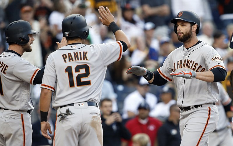 San Francisco Giants' Conor Gillespie, left, and Joe Panik congratulate Brandon Belt, right, after his grand slam against the San Diego Padres during the fifth inning of a baseball game in San Diego, Friday, April 7, 2017. (AP Photo/Alex Gallardo)