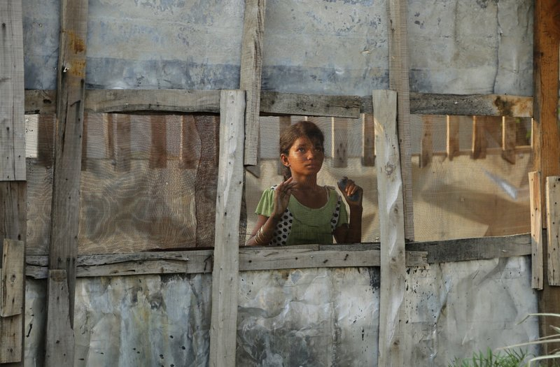 In this Wednesday, Aug. 16, 2017, file photo, a Rohingya refugee girl looks through a mesh window at a camp set up for the refugees on the outskirts of Jammu, India. A day after the U.N. chief voiced concern about Indian plans to potentially deport tens of thousands of Muslim Rohingya refugees, an Indian government official said Wednesday that authorities are only working to identify those who fled persecution in neighboring Myanmar, not expel them. An estimated 40,000 Rohingya Muslims have taken refuge in various parts of India, though fewer than 15,000 are registered with the U.N. High Commissioner for Refugees.