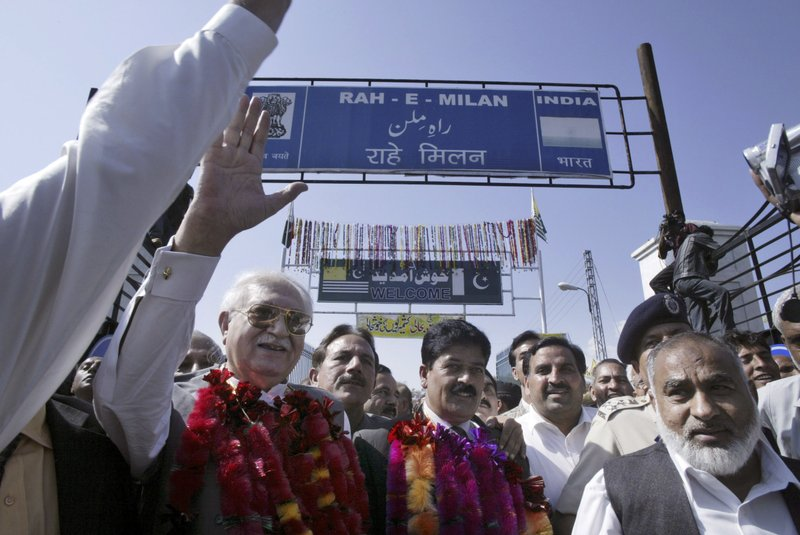 In this Oct. 22, 2008, file photo, President of Pakistan-administered Kashmir, Raja Zulqarnain Khan waves after flagging off trucks to the Indian side of the Line of Control, the de facto border in Kashmir, in the Poonch-Rawalakot area, about 250 kilometers (156 miles) from Jammu, India. India and Pakistan opened a trade route between the two sides of the divided Himalayan region for the first time in six decades.