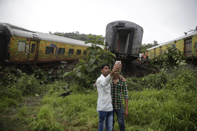 Indian boys take a selfie near derailed coaches of the Duronto Express in Asangaon, some 70 kilometers from Mumbai, India, Tuesday, Aug. 29, 2017. A passenger train partly derailed Tuesday morning in western India, the third rail accident in the country in 10 days. Rescuers were working to pull out people who were trapped in the toppled train engine and seven coaches lying on their sides. No casualties or injuries have been reported, railway spokesman A.K. Jain said.
