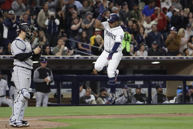 San Diego Padres' Yangervis Solarte, right, reacts after hitting a two-run home run as Colorado Rockies catcher Tony Wolters waits at left, during the sixth inning of a baseball game Tuesday, May 2, 2017, in San Diego. (AP Photo/Gregory Bull)
