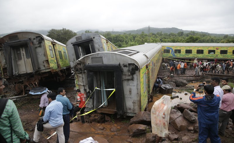 Workers repair the track near upturned coaches of the Duronto Express in Asangaon, some 70 kilometers from Mumbai, India, Tuesday, Aug. 29, 2017. A passenger train partly derailed Tuesday morning in western India, the third rail accident in the country in 10 days. Rescuers were working to pull out people who were trapped in the toppled train engine and seven coaches lying on their sides. No casualties or injuries have been reported, railway spokesman A.K. Jain said.