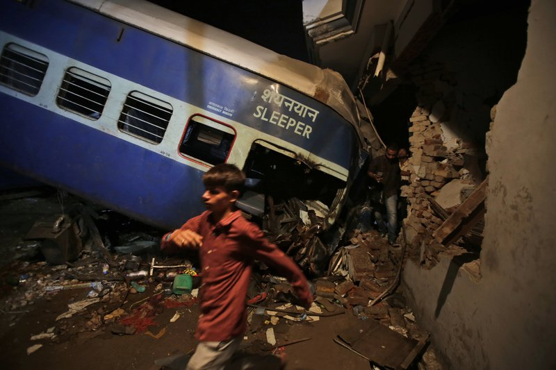 An Indian boy walks past the upturned coaches of the Kalinga-Utkal Express after an accident near Khatauli, in the northern Indian state of Uttar Pradesh, India, Sunday, Aug. 20, 2017. Six coaches of a passenger train derailed in northern India on Saturday, killing more than 20 people and injuring dozens, officials said.