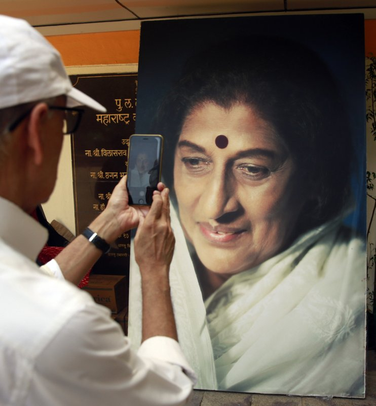 A man takes a photograph of a giant portrait of Indian musician Kishori Amonkar in Mumbai, India, Tuesday, April 4, 2017. Amonkar, renowned for her innovative interpretation of classical Indian music, has died, one of her students said Tuesday. She was 84.