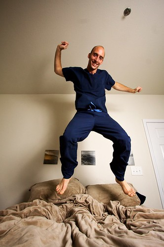 Smiling nurse jumping on a bed