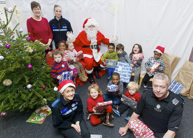 Women and men in uniform bringing presents to young children