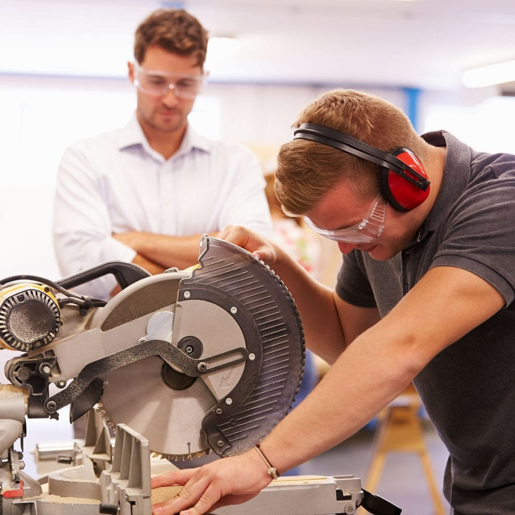 young man being trained on how to use a miter saw with instructor watching in background