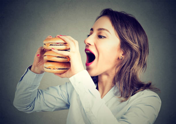 open wide woman eating big burger