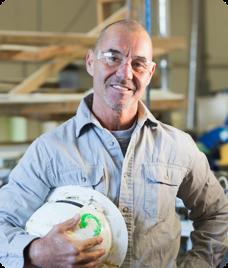 an elderly man holding a white helmet