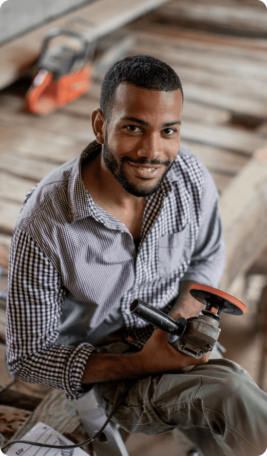 smiling man holding a construction tool