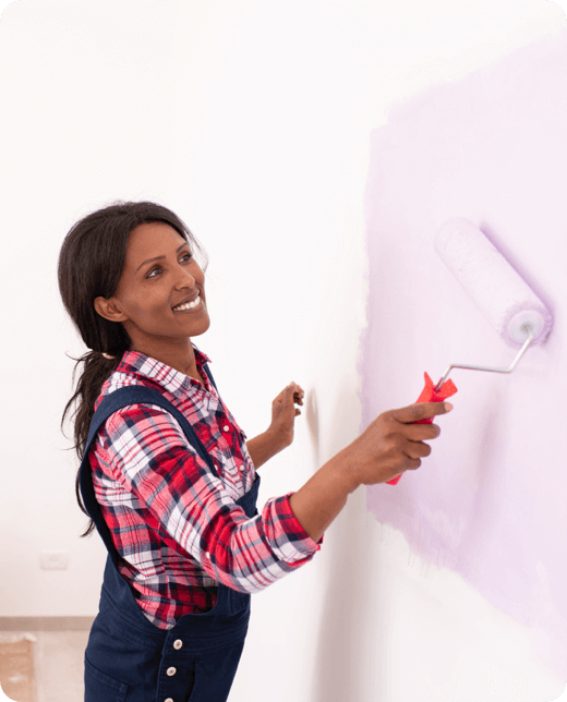 a smiling woman painting a wall pink
