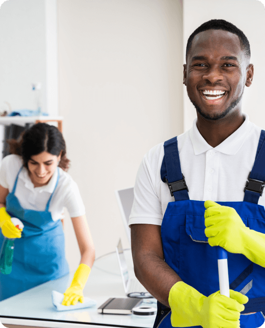 a young man smiling at the camera while another woman cleaning the table top