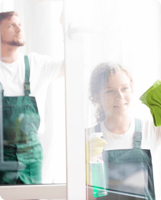 two people in green uniform cleaning windows