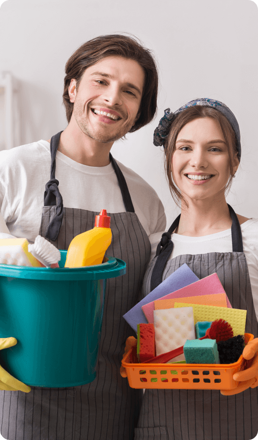 two smiling people holding a basket of cleaning materials
