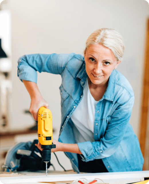 a woman looking at the camera while drilling a piece of wood