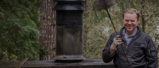 a man standing beside a chimney while holding a cleaning brush
