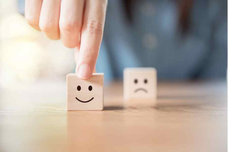 Two cubes - one with sad face and another with a smiling face. A man chooses the happy face.