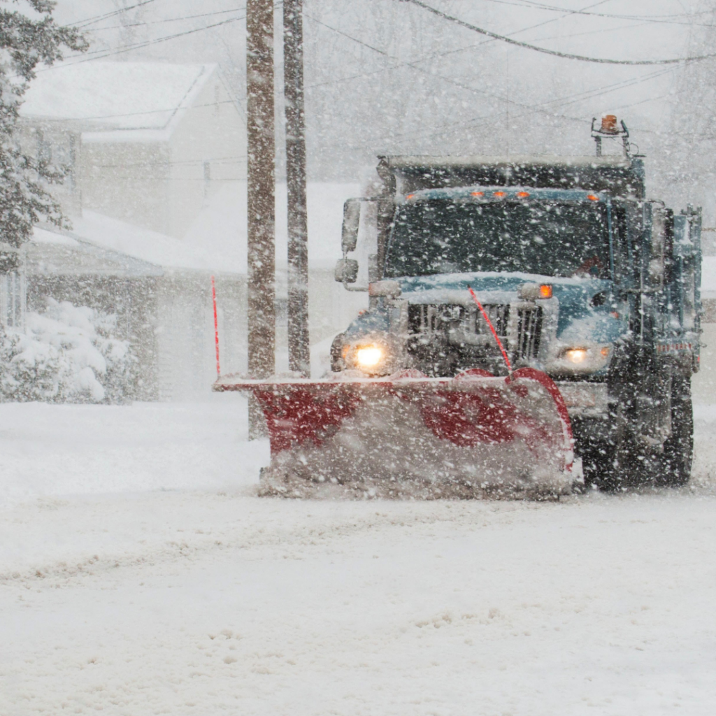 Snow plow clearing streets during a snow storm