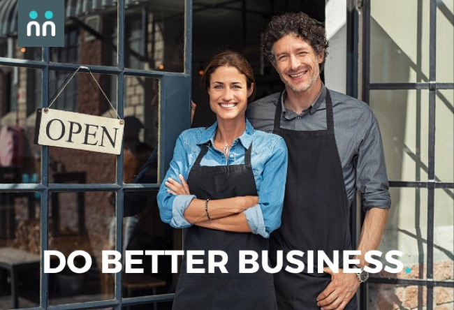 """Business owners smiling in front of their shop which says, """"open."""""""