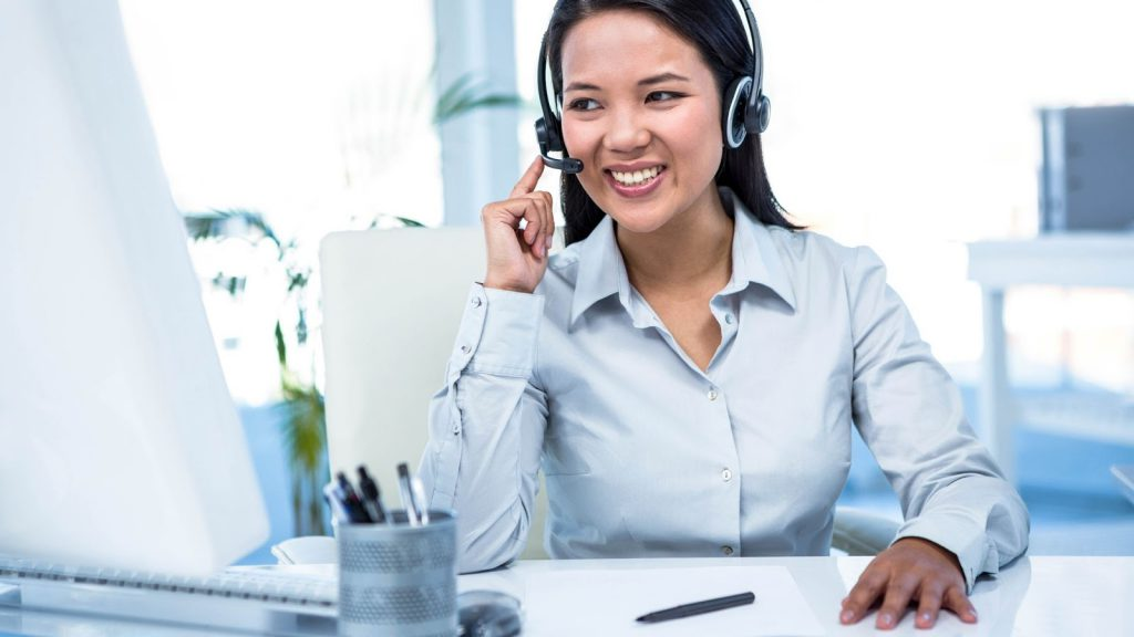 Smiling answering agent in white room setting online appointment for caller