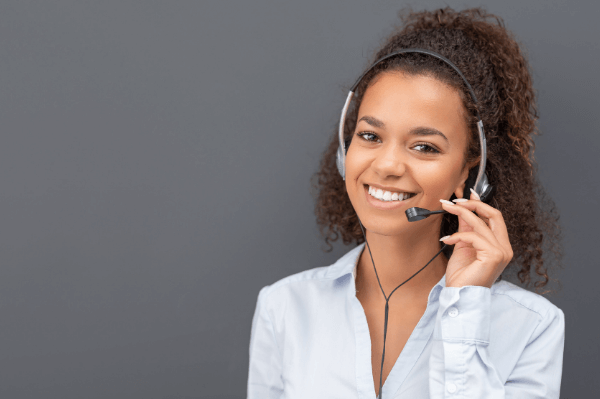 Smiling woman on a headset, answering calls to ensure there are no missed customer calls