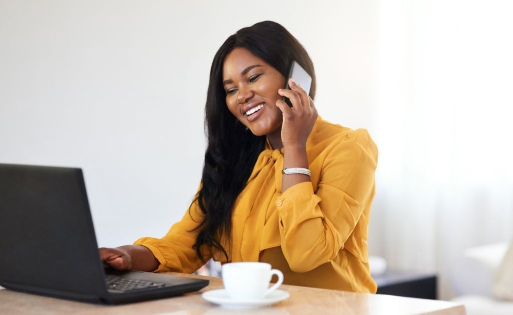 Woman using her phone to talk with a small business call answering service