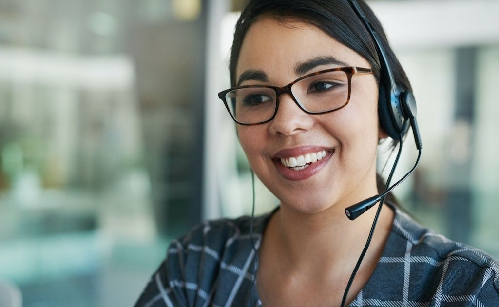 Woman on a headset, answering calls as part of a telephone answering service.