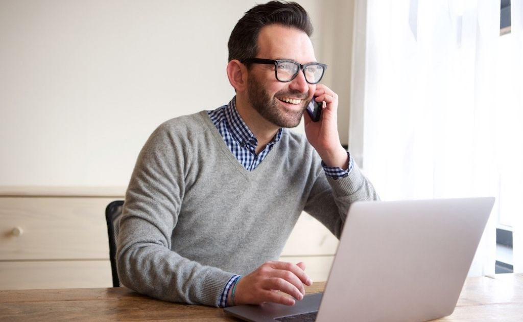 Smiling man on a mobile phone, sitting at a desk with a laptop.