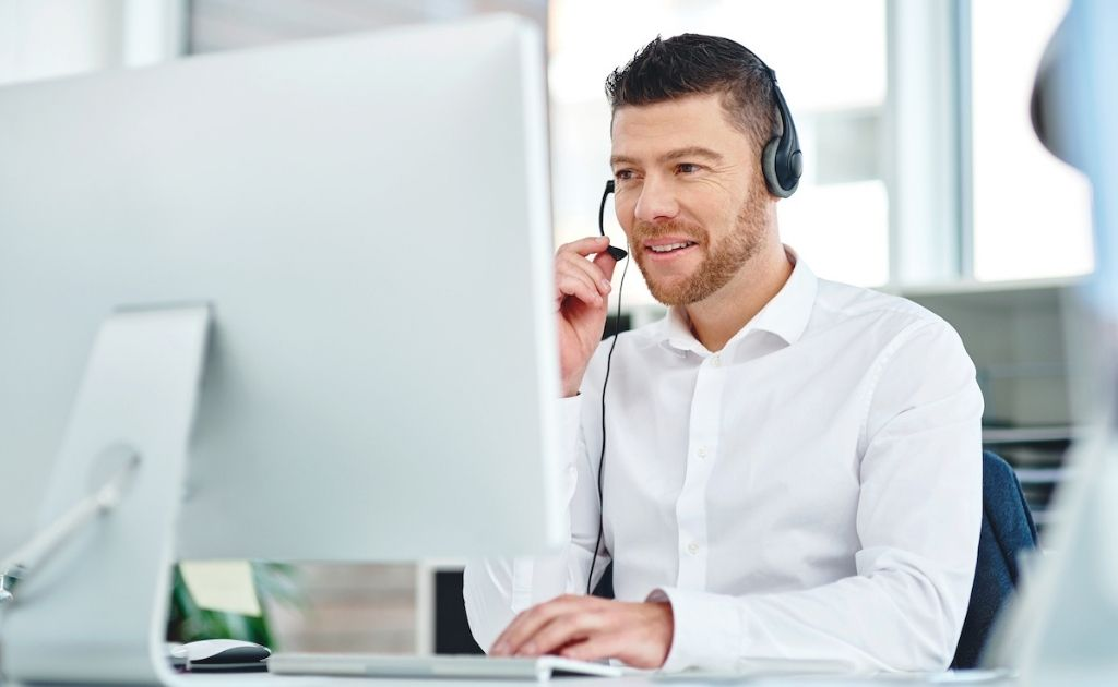 Man on a headset, sitting in front of a laptop, answering calls as part of a telephone answering service.