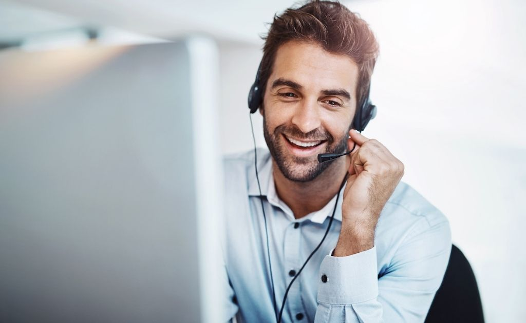 Smiling man answering calls using a headset as part of a telephone answering service job.