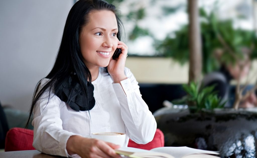 Smiling woman on the telephone, dealing with an angry caller.