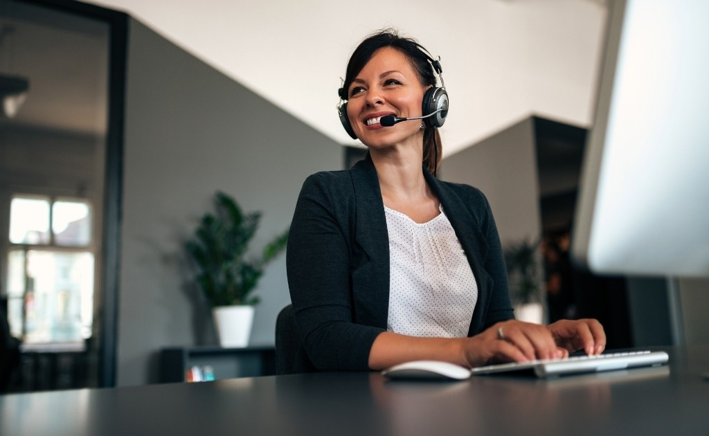 Smiling Woman working in an office environment, taking calls for her call handling service job.